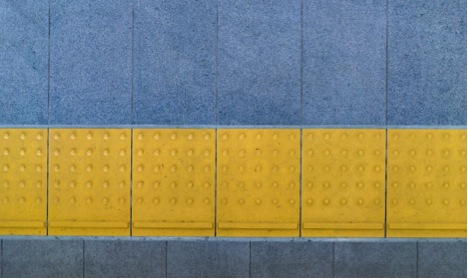 yellow detectable warning surface next to sidewalk