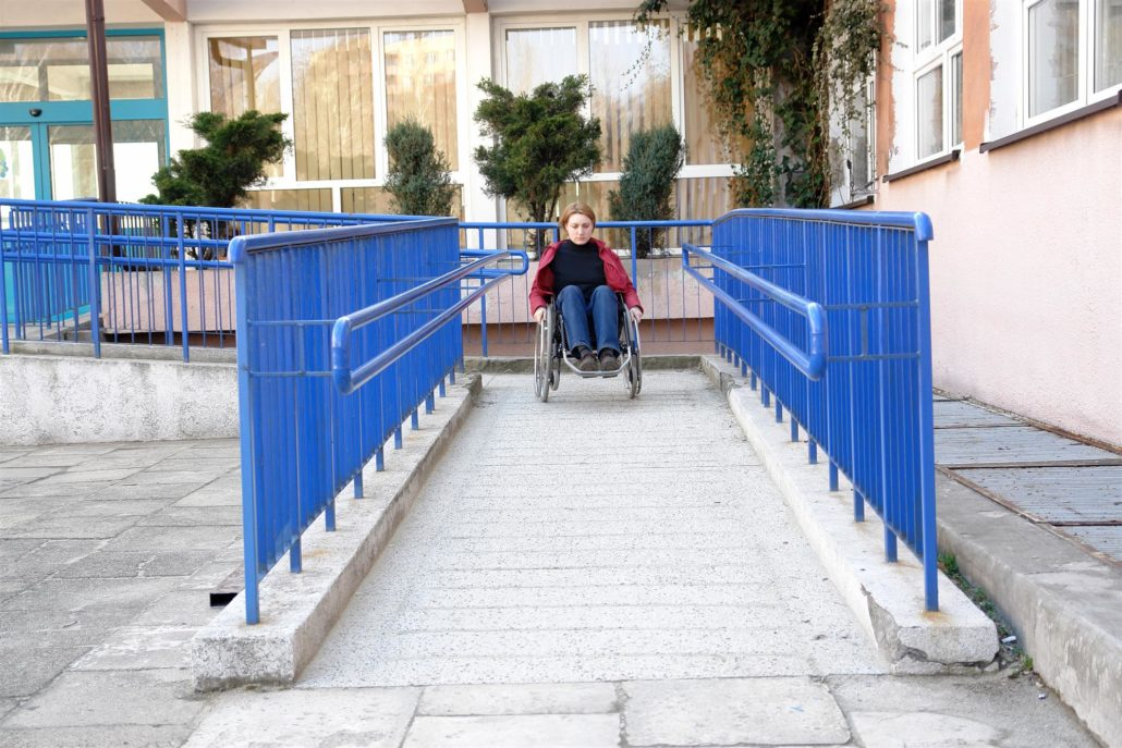 Handicapped woman on wheelchair using ramp for disabled