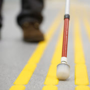 Blind pedestrian walking on tactile paving