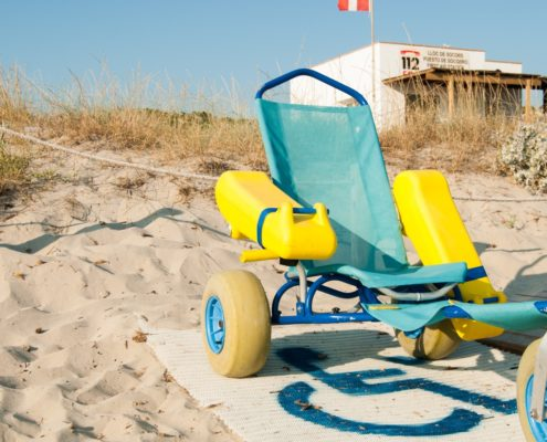 A beach wheelchair parked on a sandy beach