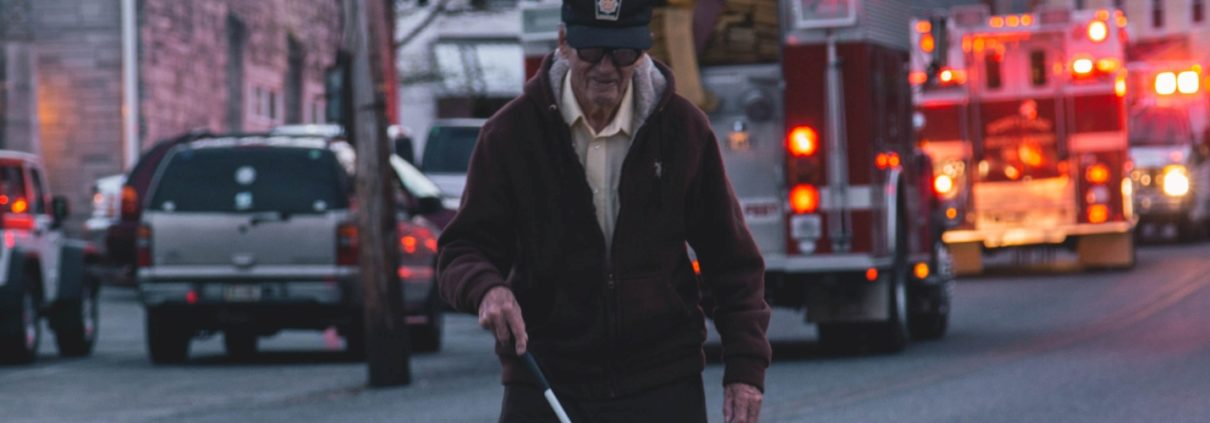 Blind man with a white cane walking on the road