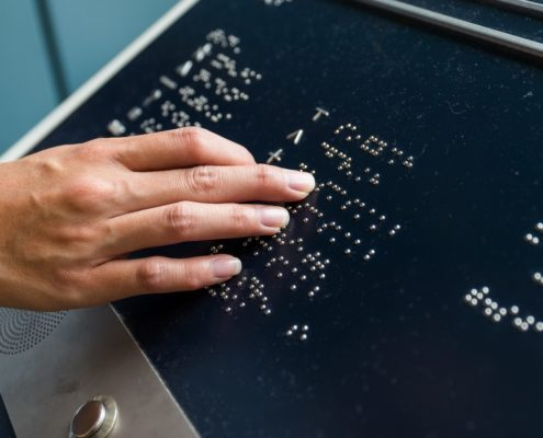 A sight impaired person using a braille directory at a building to find an office