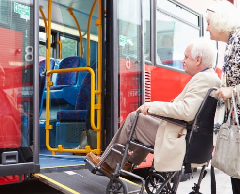 An elderly couple using the wheelchair ramp on a bus