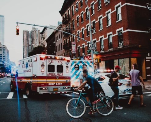Ambulance and cars driving over a pedestrian crosswalk in a the city