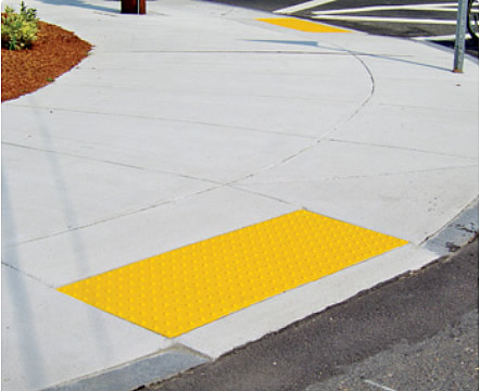 A curb ramp which has a yellow detectable surface ramp installed