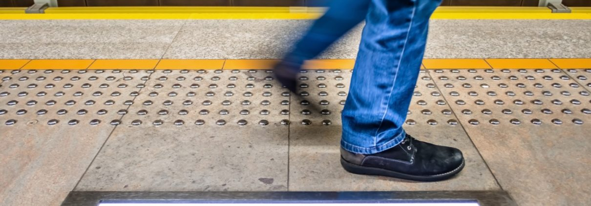 one pedestrian walks on the subway platform along detectable warning surfaces