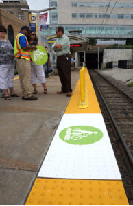 People standing at a station behind the detectable warning surface