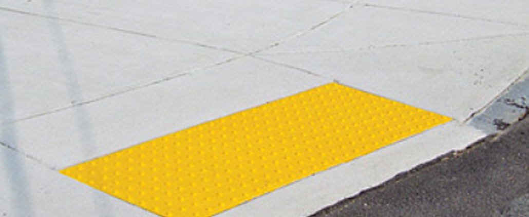 A sidewalk curb ramp which has a yellow detectable surface ramp installed