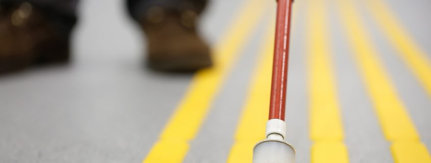 white walking cane positioned between tactile yellow lines