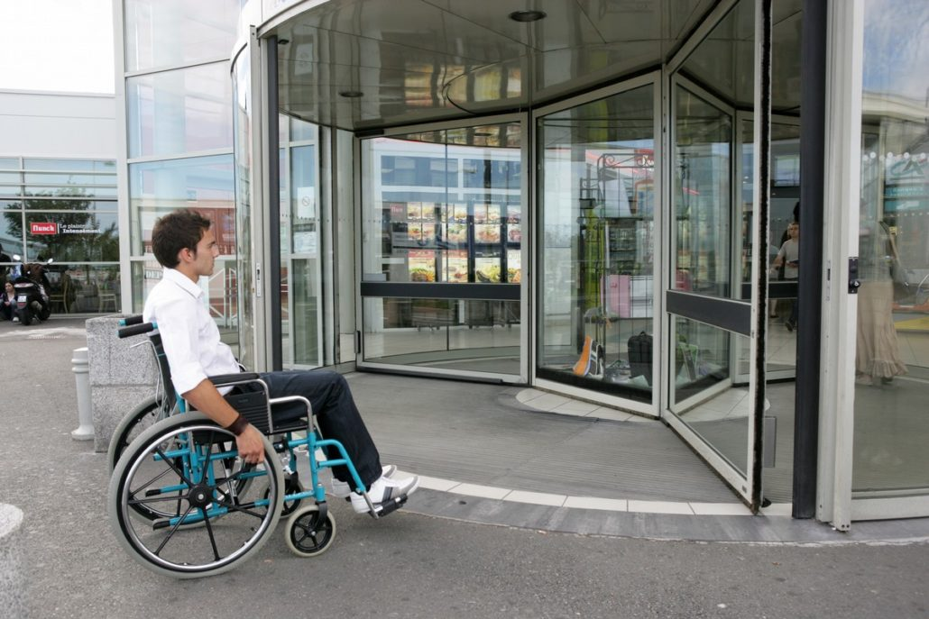 man in wheelchair in front of a shopping store