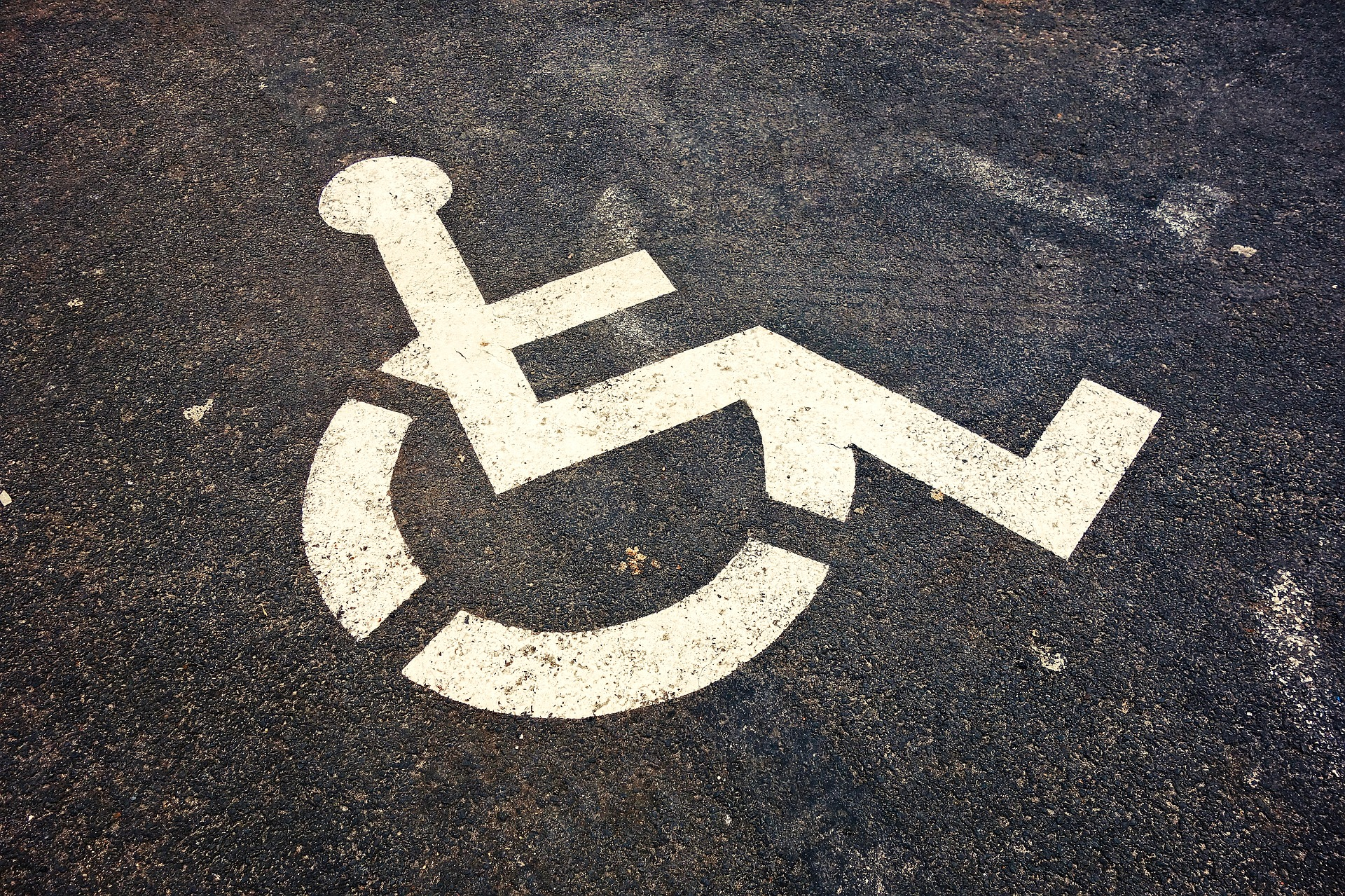 White Wheelchair Graphic on Black Asphalt