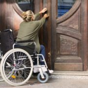 woman in wheelchair in front of entrance door trying to get in