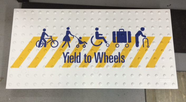 Yield to Wheels Graphic on Detectable Warning Surface