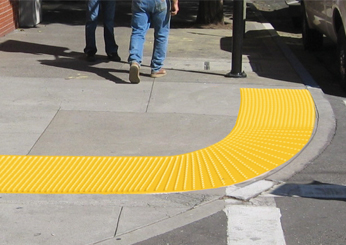 curved detectable warning tiles on sidewalk.