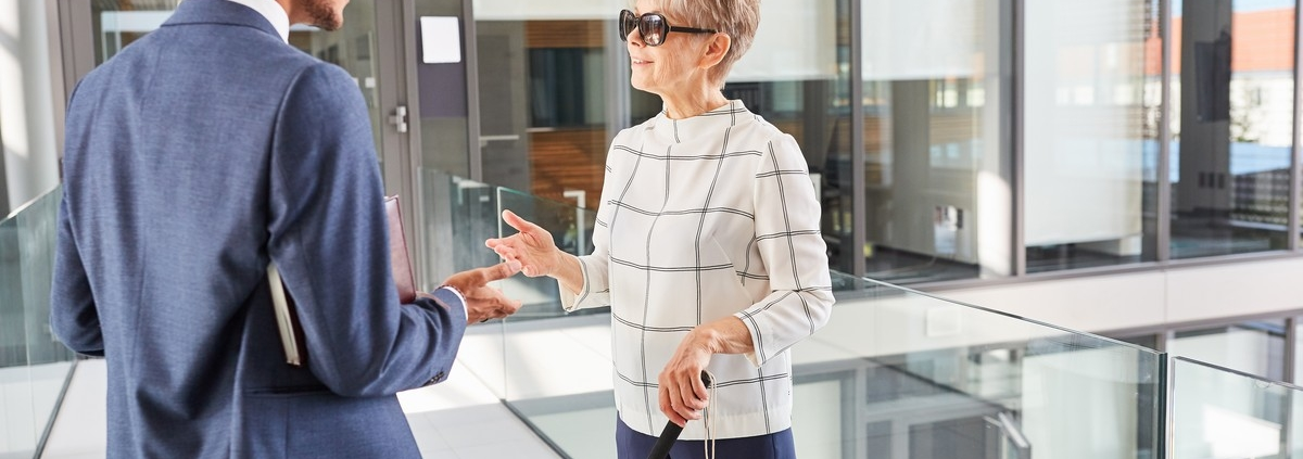 A businessman talking with a client who is visually impaired