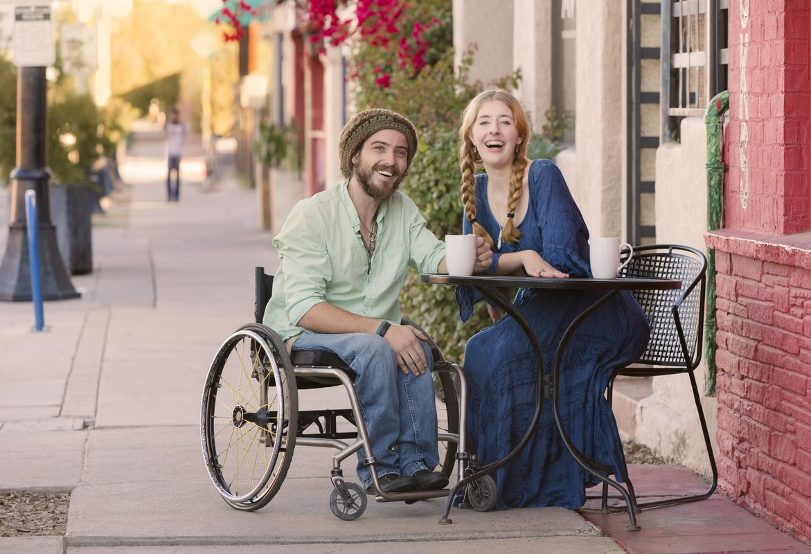 A woman and a man who is a wheelchair user having coffee together