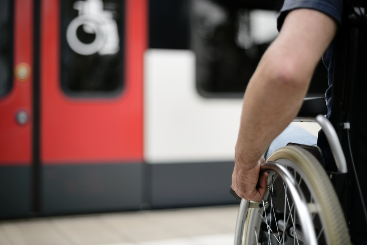 Person wheelchair user at station at barrier free accessibility compartment sign mobility transport
