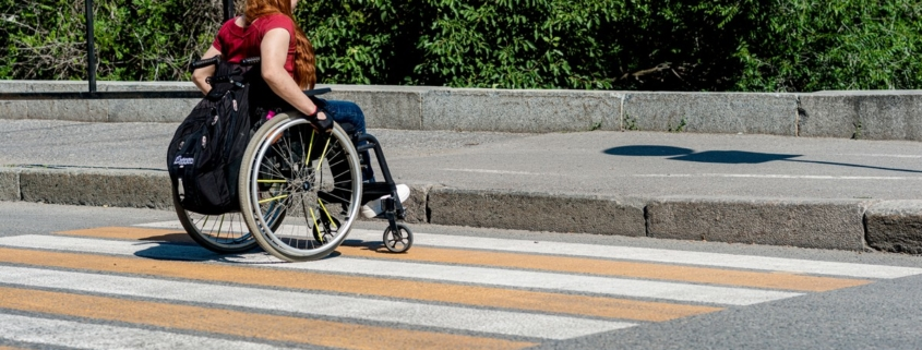 A young woman in a wheelchair in front of a high curb at a pedestrian crossing