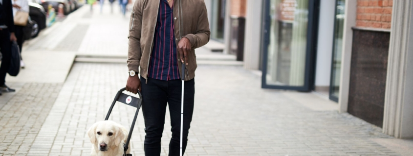 african american disabled man walking with friendly dog