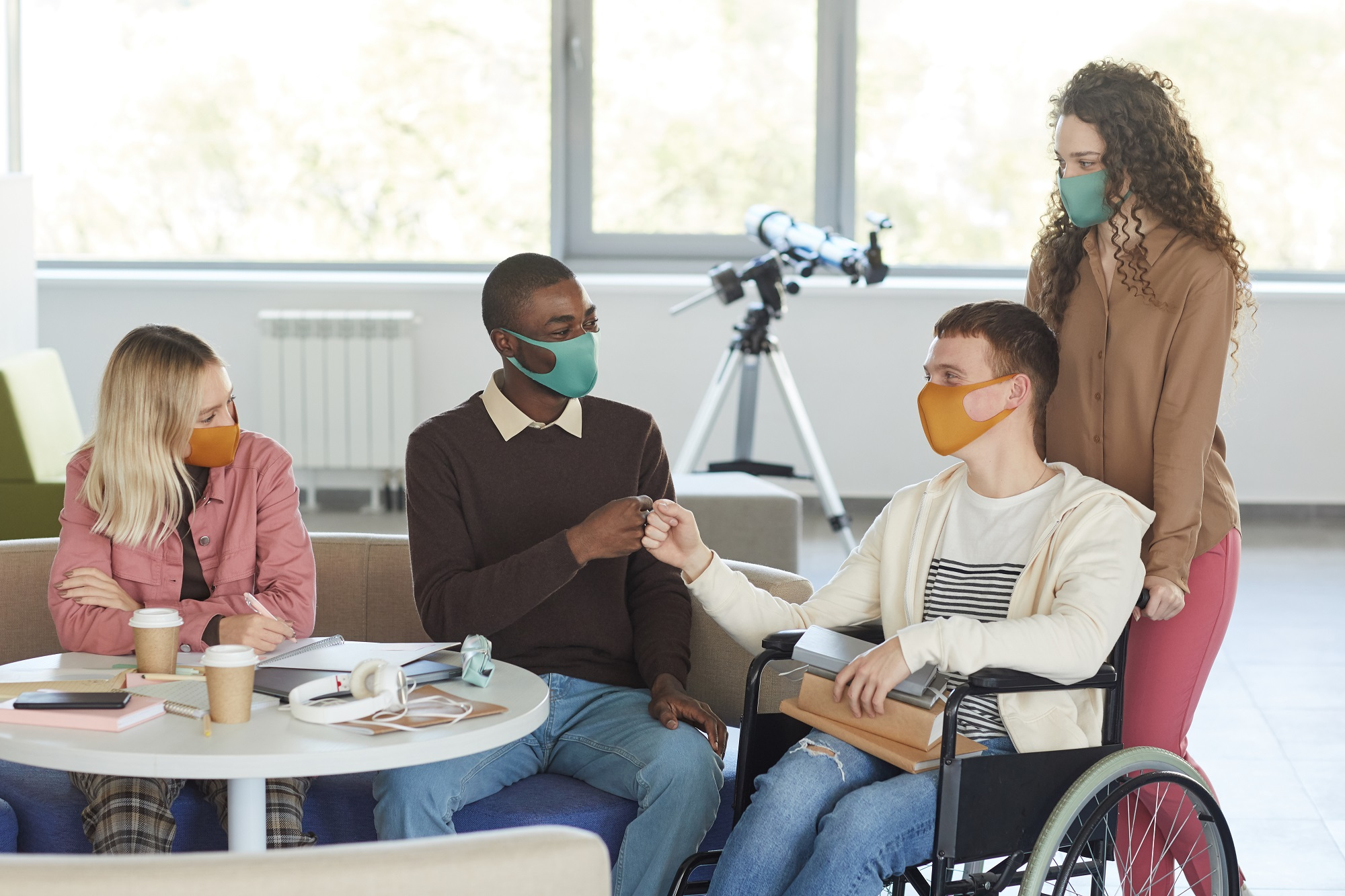 group of students wearing masks in college with young man using wheelchair