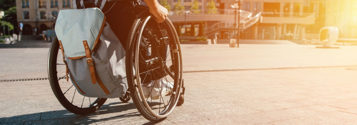 cropped panoramic view of man using wheelchair with bag on street with sunlight