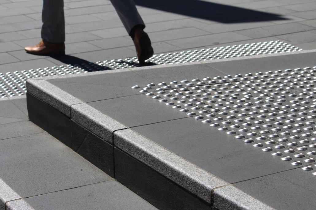 The steps have stainless steel tactile indicator studs that have been installed in a grid formation