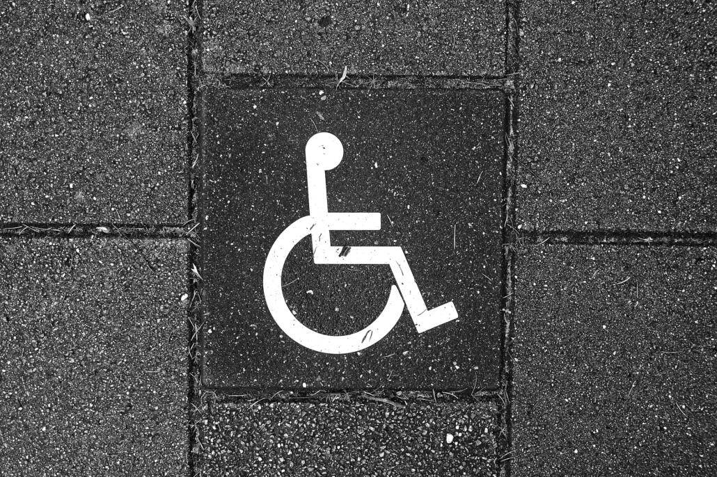 White Handicap Sign Painted on Dark Asphalt
